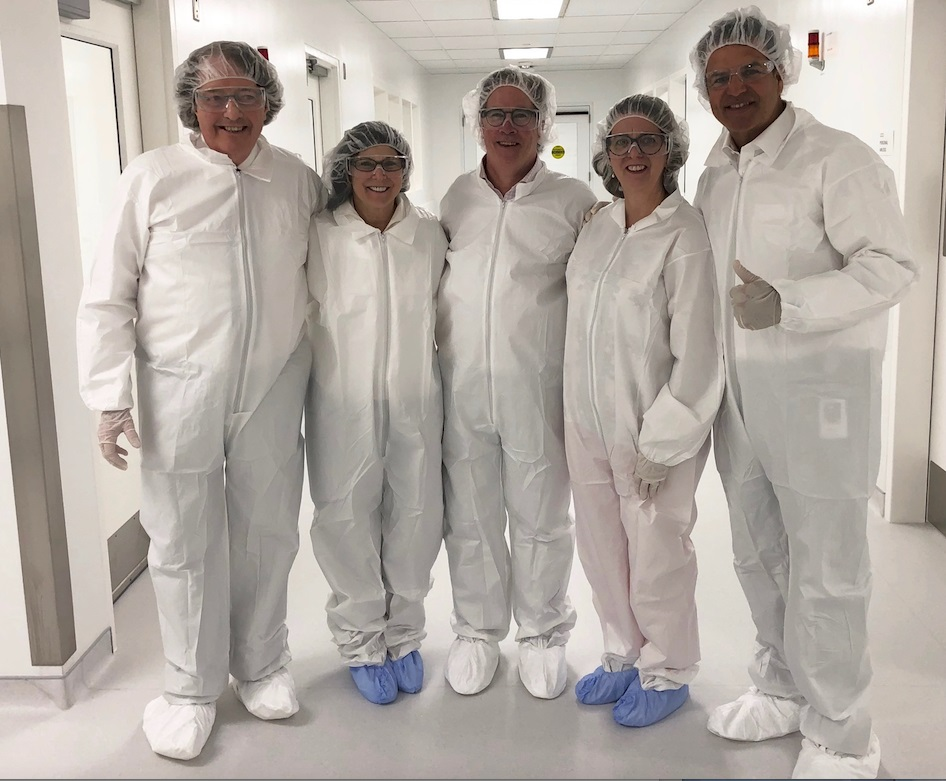 Wearing clean suits outside of a lab are Dr. Brian G.M. Durie, Susie Durie, Michael Tuohy, Robin Tuohy, and Chad Saward